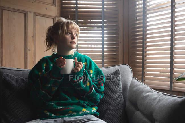 Donna che prende un caffè mentre è seduta sul divano a casa — Foto stock