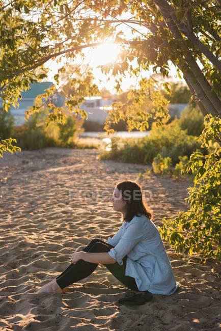 Frau entspannt sich an einem sonnigen Tag am Flussufer — Stockfoto