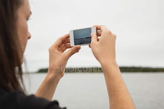Close-up of woman clicking photos with mobile phone near riverside — Stock Photo
