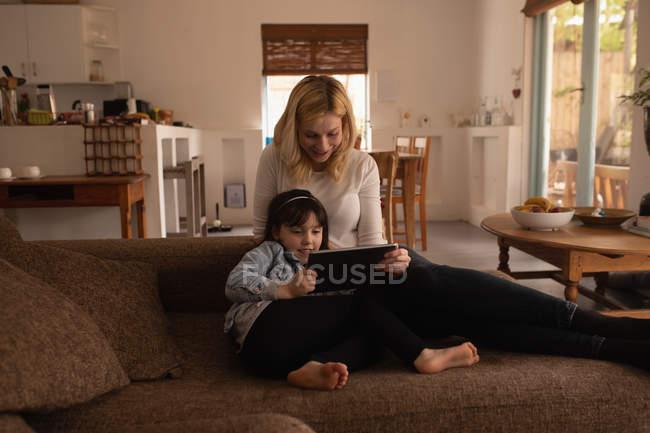 Madre e figlia utilizzando tablet digitale in soggiorno a casa — Foto stock