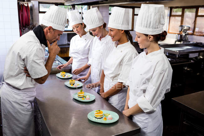 Head chef inspecting dessert plates in restaurant — Stock Photo