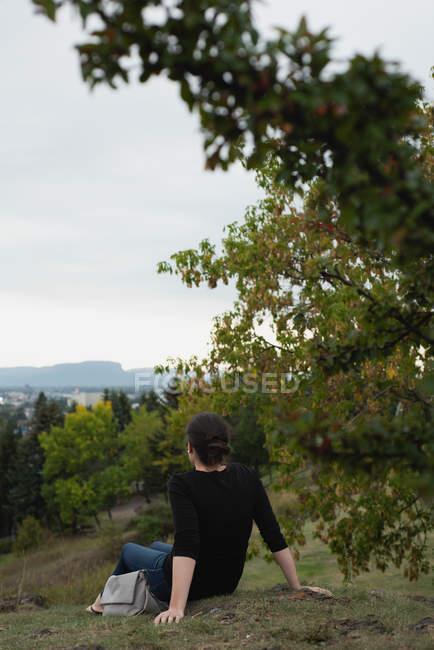 Vista posteriore della donna che si siede sulla collina e guardando vista — Foto stock