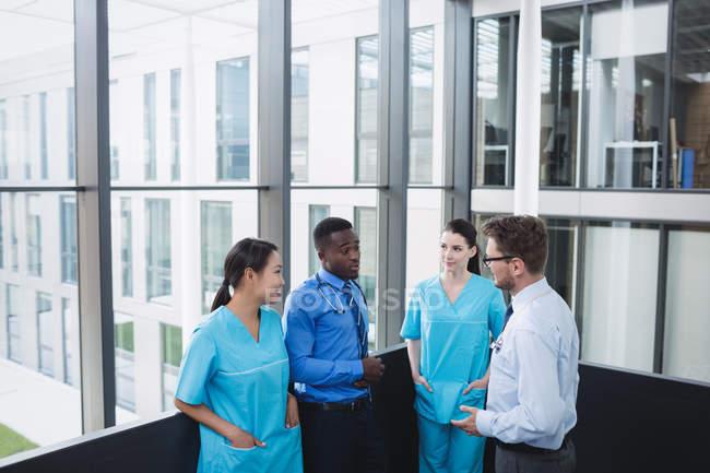 Médicos y enfermera interactuando entre sí en el hospital - foto de stock