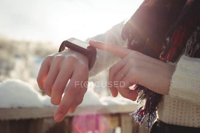 Metà sezione di donna controllando il suo smartwatch — Foto stock