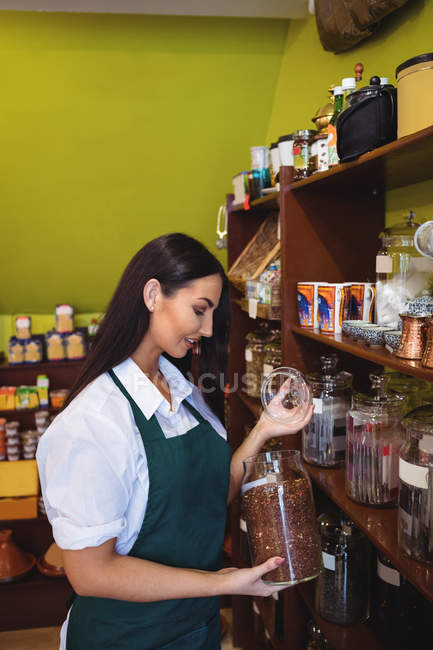 Жіночий крамар, тримаючись за jar пряностей магазин — стокове фото
