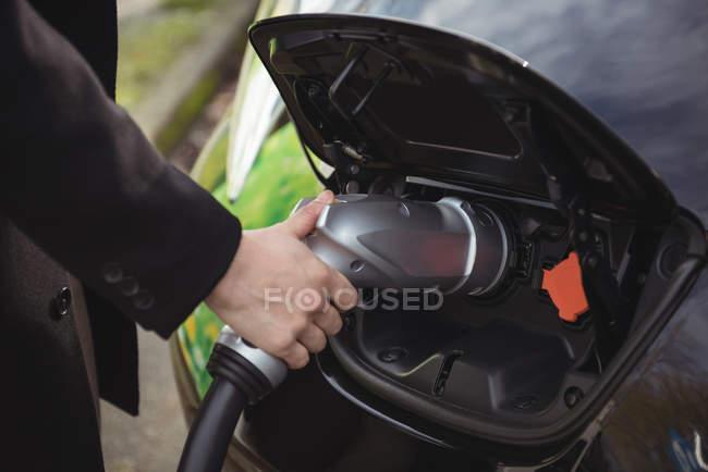Partie médiane de l'homme chargeant la voiture à la station de recharge du véhicule électrique — Photo de stock