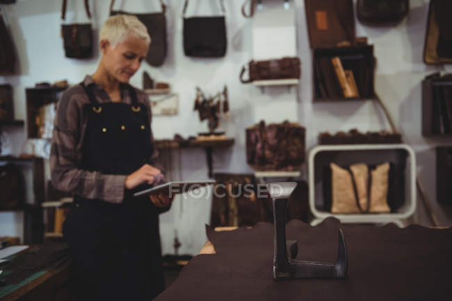 Mature craftswoman using digital tablet in workshop — Stock Photo