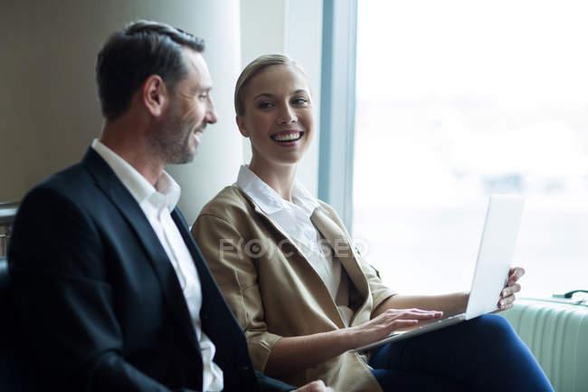 Gli uomini d'affari discutono di laptop in aeroporto — Foto stock