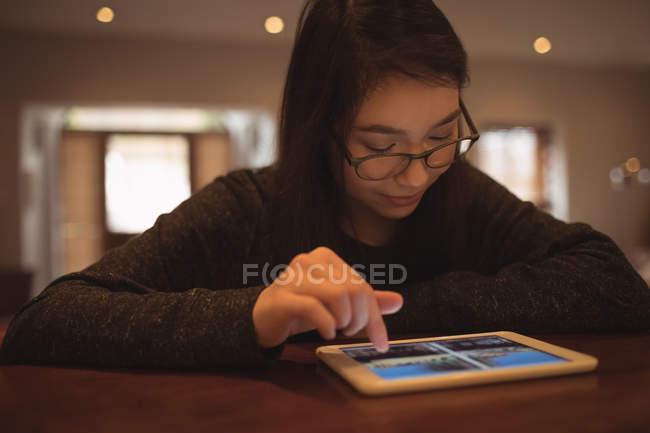 Mujer usando tableta digital en la mesa en casa - foto de stock
