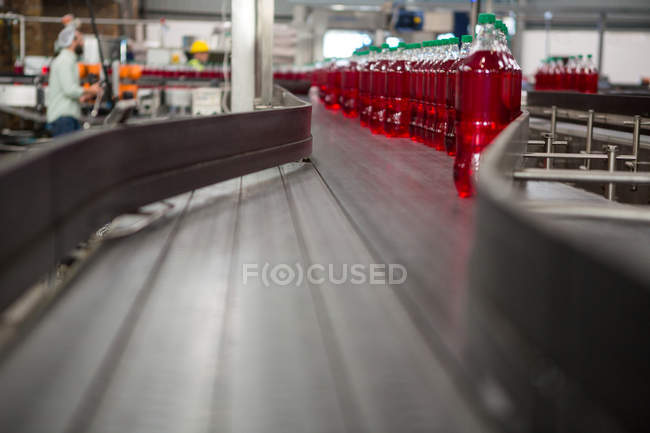 Red juice bottles on production line in manufacturing industry — Stock Photo
