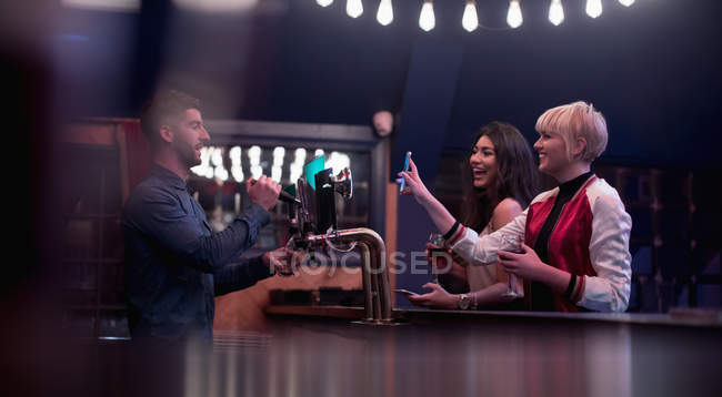 Bartender interacting with beautiful women at counter in bar — Stock Photo