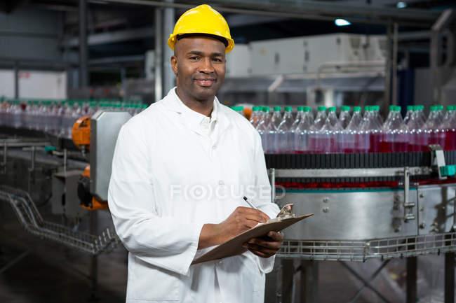 Портрет улыбающегося работника мужского пола, отмечающего продукцию на складе — стоковое фото