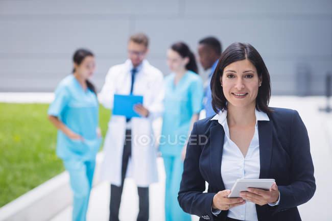 Портрет усміхнене жіночий лікар холдингу цифровий планшетний приміщення лікарні — стокове фото