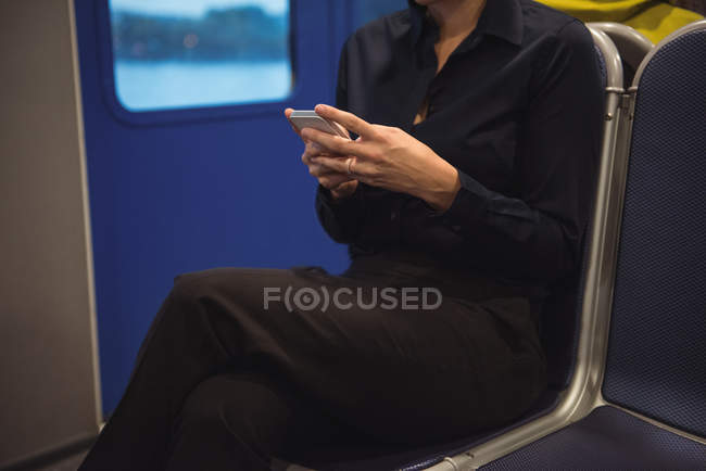 Mid-section of businesswoman using phone while sitting in train — Stock Photo