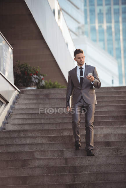 Businessman using mobile phone while walking down steps — Stock Photo