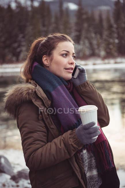 Frau am Ufer stehend und mit Handy im winter — Stockfoto