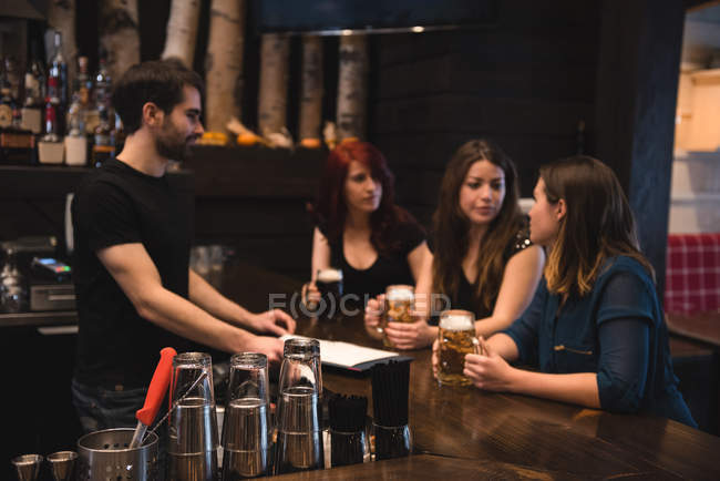Friends holding beer glasses at bar counter and interacting with bartender — Stock Photo