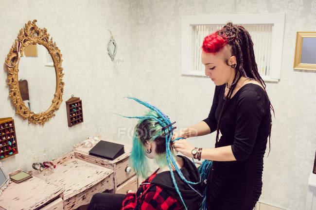 Estetista styling clienti capelli in dreadlocks negozio — Foto stock