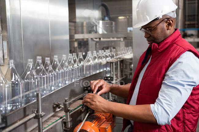 Confident male worker operating machine in juice factory — Stock Photo