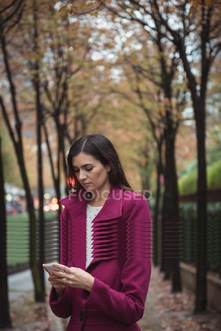 Femme d'affaires utilisant téléphone debout sur le chemin avec des arbres — Photo de stock