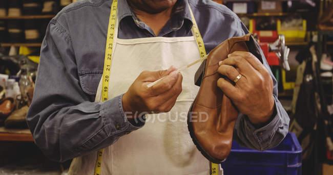 Mittelteil des Schuhmachers, der in der Werkstatt Kleber auf den Schuh klebt — Stockfoto