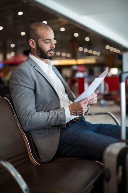 Empresario leyendo un documento en la sala de espera en terminal del aeropuerto - foto de stock