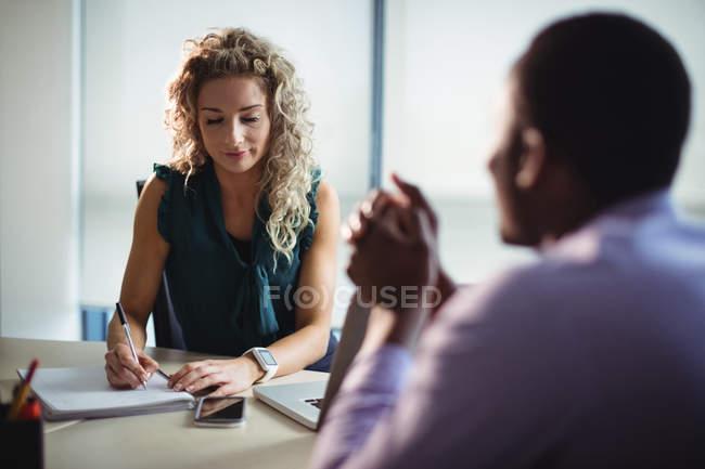Geschäftsfrau und Geschäftsmann interagieren im Amt miteinander — Stockfoto