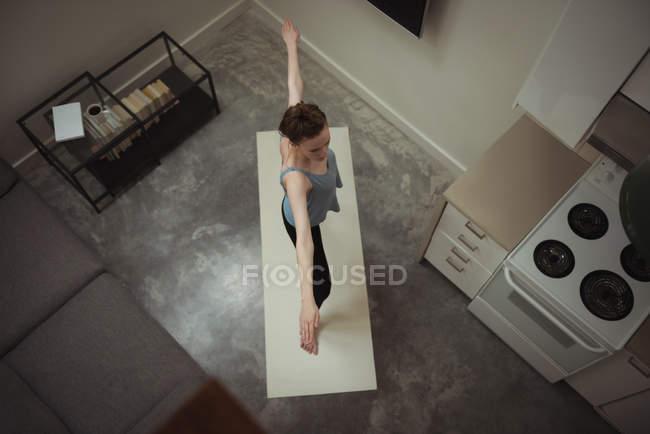 Femme effectuant des exercices de yoga étirement dans la cuisine à la maison — Photo de stock