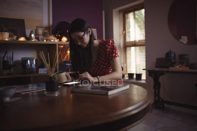 Woman using mobile phone while having coffee at home — Stock Photo