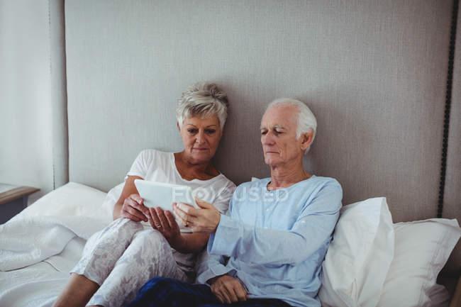 Couple aîné utilisant une tablette numérique sur le lit dans la chambre à coucher — Photo de stock