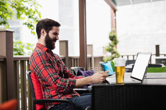 Man using mobile phone while sitting in bar — Stock Photo