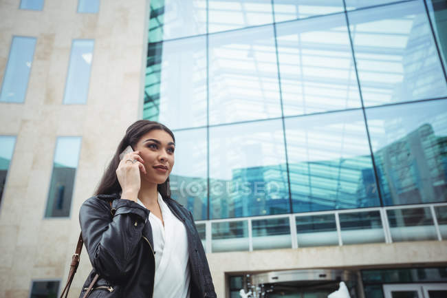 Woman talking on mobile phone outside the office premises — Stock Photo