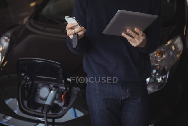 Section de l'homme à l'aide de tablette numérique et téléphone mobile pendant le chargement de la voiture électrique dans garage — Photo de stock