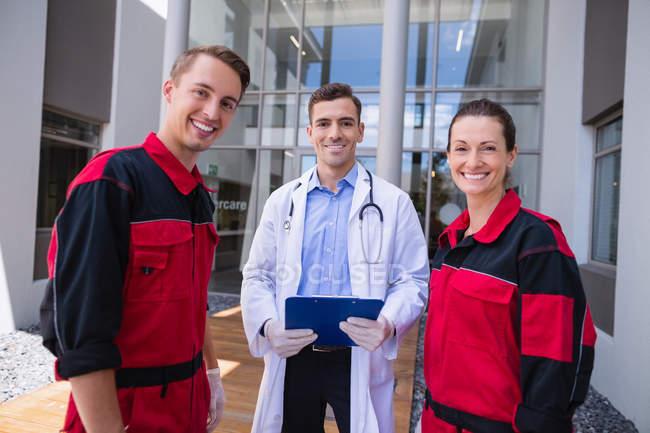 Portrait de médecin souriant et ambulancier debout à l'hôpital — Photo de stock