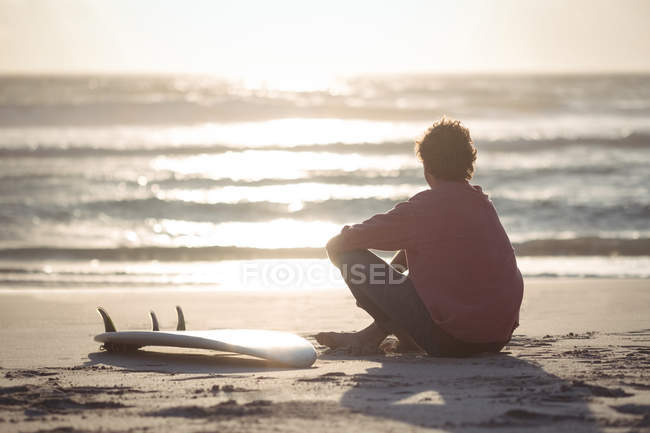 Man with surfboard sitting on beach at dusk — Stock Photo