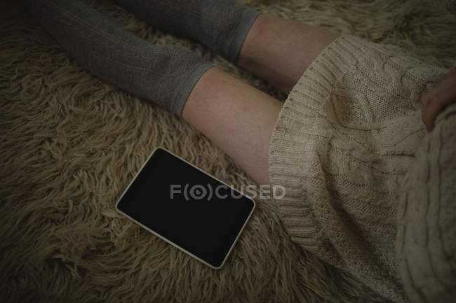 Woman sitting on the floor with digital tablet at home — Stock Photo