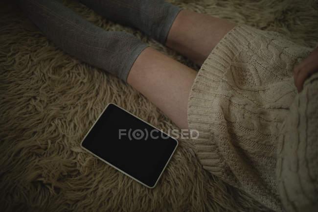 Femme assise sur le sol avec tablette numérique à la maison — Photo de stock
