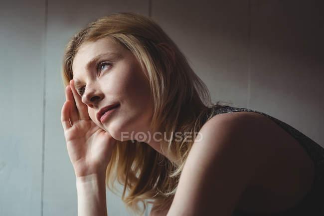 Donna premurosa seduta con la mano sulla fronte a casa — Foto stock