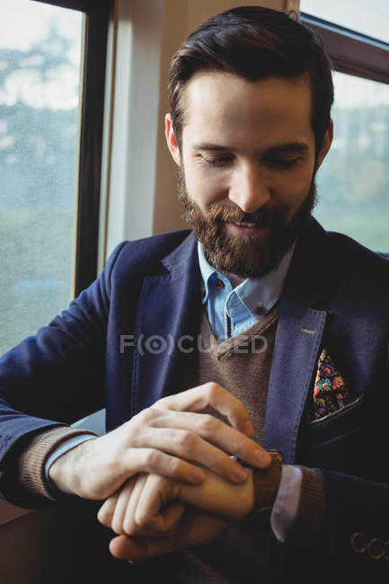 Businessman checking time on watch while travelling in train — Stock Photo
