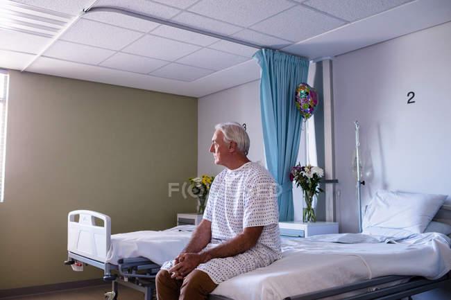 Paciente mayor masculino reflexivo sentado en la sala del hospital - foto de stock