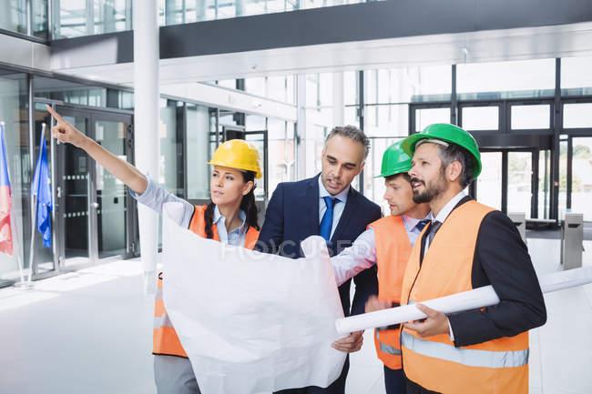 Бизнесмен обсуждает проект с архитекторами в офисном здании — стоковое фото