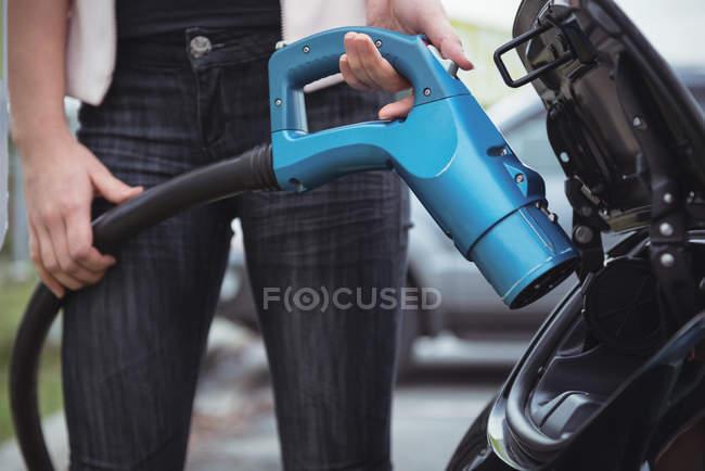 Partie médiane de la femme charge voiture électrique sur la rue — Photo de stock