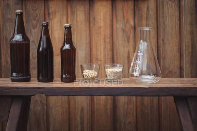 Домашнее пиво бутылки и ингредиенты с конической колбе для домашней пивоварни — стоковое фото