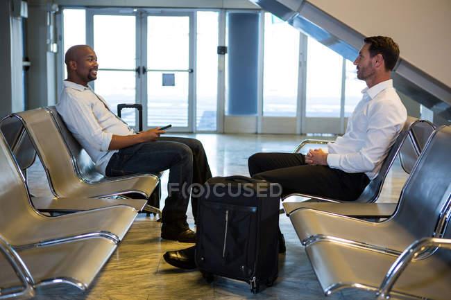 Пассажиры с чемоданом в зоне ожидания в терминале аэропорта — стоковое фото