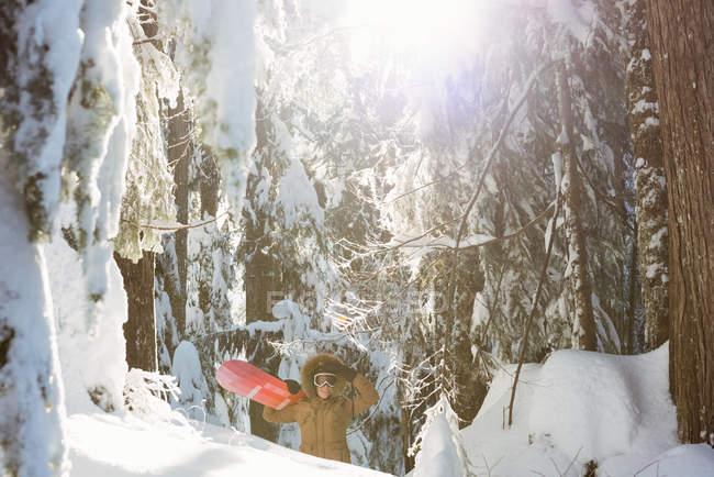 Mulher com snowboard andando na neve coberta de montanha — Fotografia de Stock