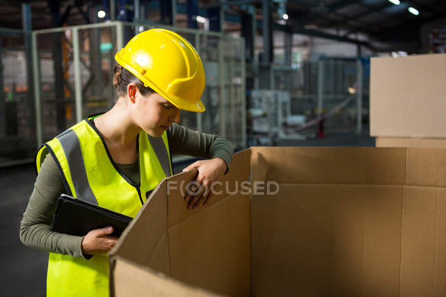 Женщина-работница проверяет продукты в коробке на складе — стоковое фото