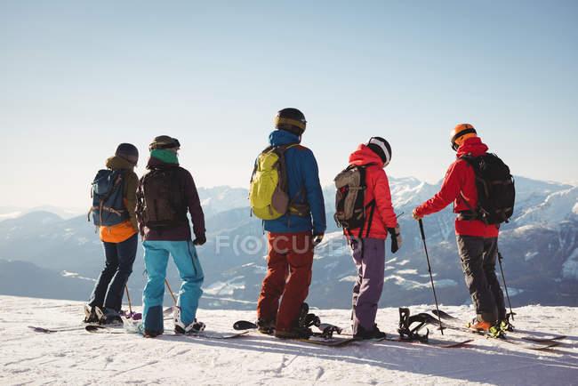 Grupo de esquiadores em pé no topo da montanha durante o inverno — Fotografia de Stock