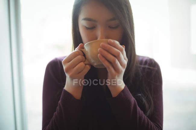 Bella donna che ha una tazza di caffè al caffè — Foto stock
