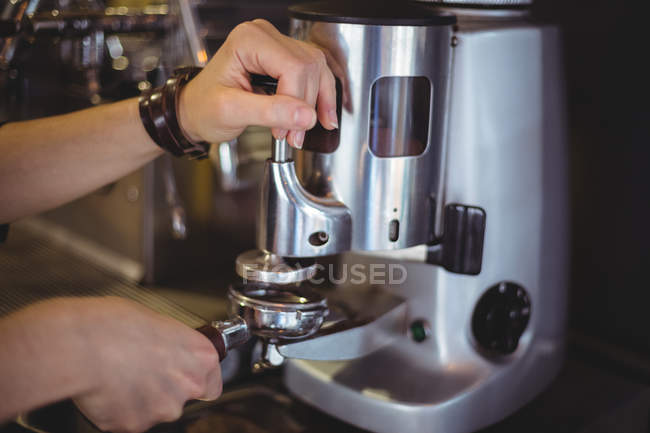 Waitress holding portafilter filled with ground coffee in cafe — Stock Photo