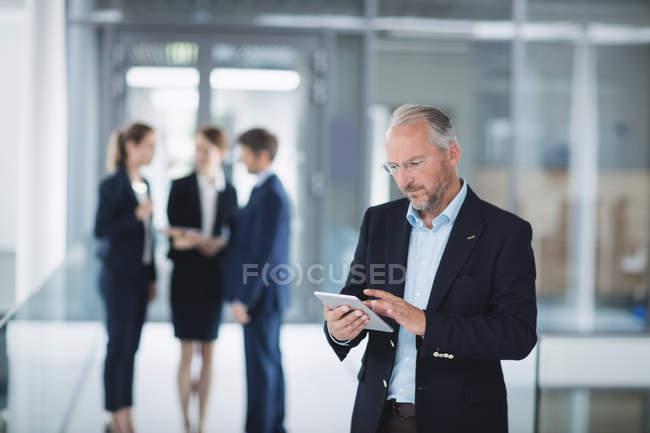 Homme d'affaires à l'aide d'une tablette numérique à l'intérieur de l'immeuble de bureaux — Photo de stock